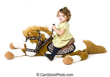 Baby girl on stuffed animal horse