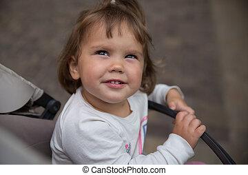 Baby girl outside sitting in a stroller