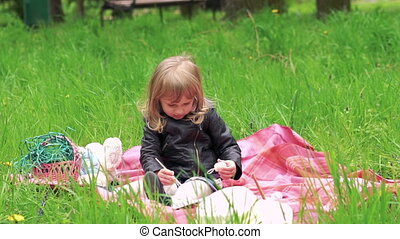 Baby-girl painting egg and smiling on a lawn in the park. Slowly