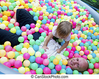 Baby girl playing in a pool of balls