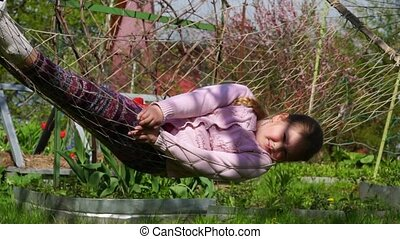 Baby girl playing in the hammock near the house (slow-mo) -...