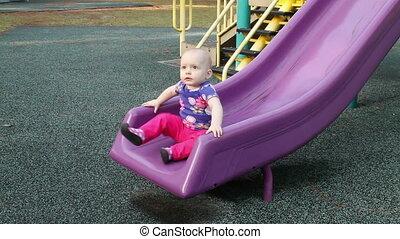Baby girl playing on slide
