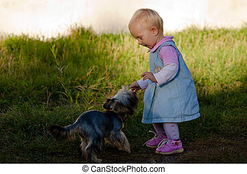 Baby girl playing with a puppy