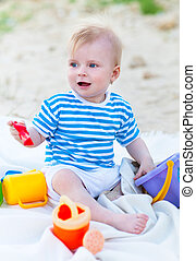 Baby girl playing with beach toys on the beach