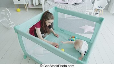 Baby girl playing with beloved mother in playpen