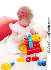Baby girl playing with bricks