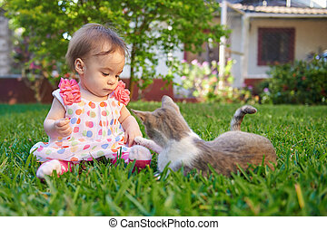 Baby girl playing with cat