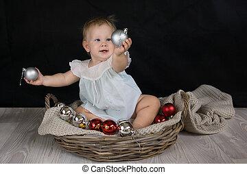 Baby girl playing with Christmas balls