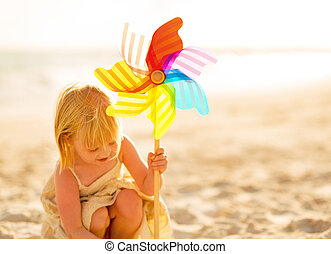 Baby girl playing with colorful windmill toy on beach
