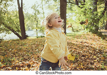 Baby girl playing with leaves in park in autumn close up