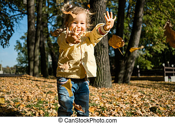Baby girl playing with leaves in park in autumn