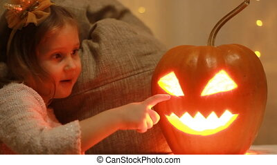 Baby girl playing with pumpkins in the Halloween.