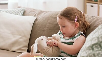 baby girl playing with toy rabbit at home - childhood and...