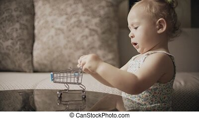 Baby girl playing with toy shopping trolley at home - Baby...