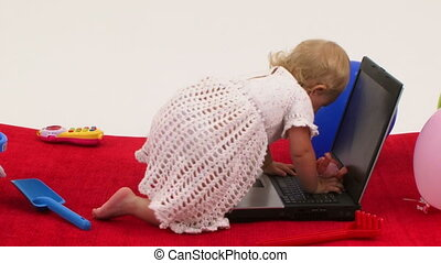 Baby girl playing with toys and climbing on laptop - Baby...
