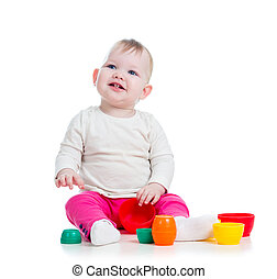 baby girl playing with toys while sitting on floor, isolated...