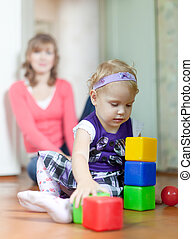 baby girl plays with blocks