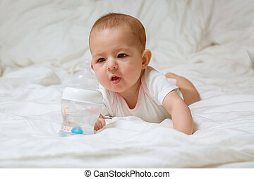 baby girl pulls hands to a bottle of water lying on a white bed. Infant in pink white clothes