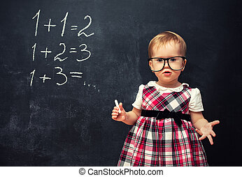 baby girl pupil in glasses and chalk at a school board with arithmetic examples
