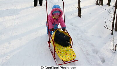 baby girl pushes sled in winter park