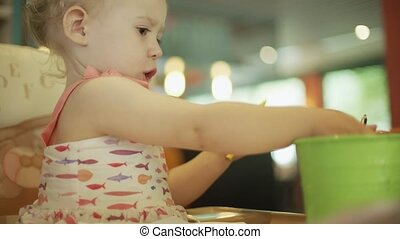 Baby girl putting color pencils into bucket on the table -...