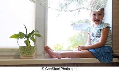 Baby girl siting on a window sill and looking out the window. The concept of expectation.
