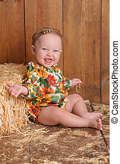 Baby Girl Sitting Against a Straw Bale