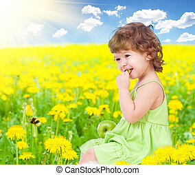 Baby girl sitting among dandelion with healthy food apple in her hands
