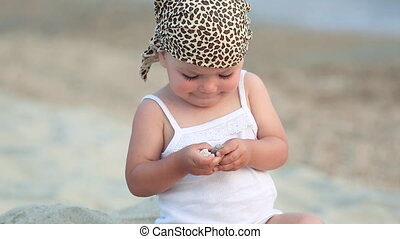 Baby girl sitting and playing on the beach