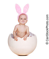 baby girl sitting in a giant easter egg shell