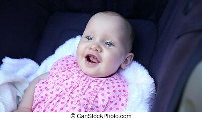 Baby girl sitting in her pram