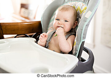 Baby girl sitting in high chair ready for eating