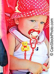 baby girl sitting in red stroller