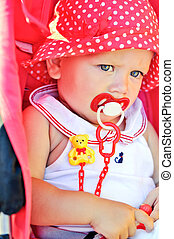 baby girl sitting in red stroller