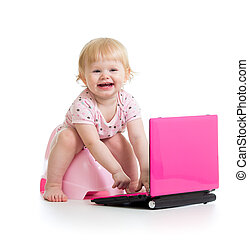 baby girl sitting on chamberpot with notebook
