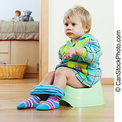 Baby girl sitting on potty in home interior