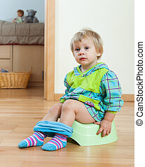 Baby girl sitting on potty in home
