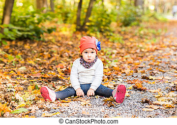 Baby girl sitting on the ground in autumn park outdoor