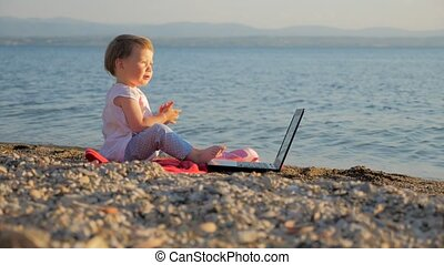 Baby girl sitting with notebook on seashore. New generation of people who combine work and vacation. Creativity and school education. Evolution and revolution at education. Successful freelancer idea