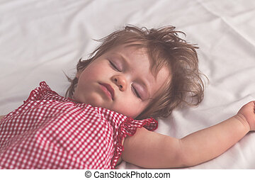 Baby girl sleeping on back with open arms and without pacifier in a bed with white sheets. Peaceful sleeping in a bright room. Close up. Pastel retro toned. Soft focus.