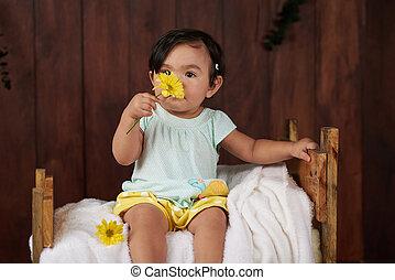 Baby girl smell flower