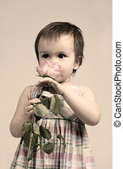 Baby girl smelling pink flower, sepia