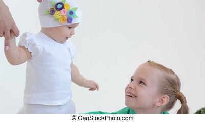Baby girl stroking her sister