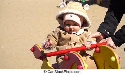Baby girl swingin on horse swing in day
