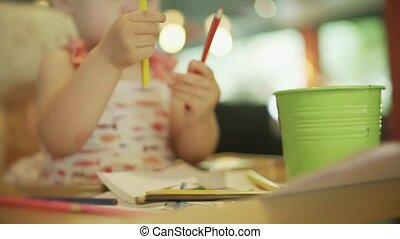 Baby girl taking color pencils out of bucket on the table -...