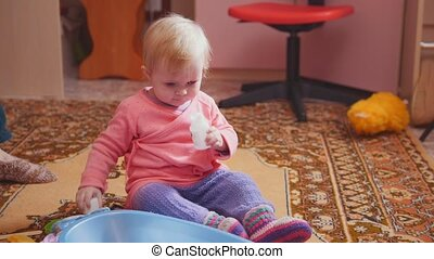 Baby girl toddler eats vitamins or pills at home, telephoto