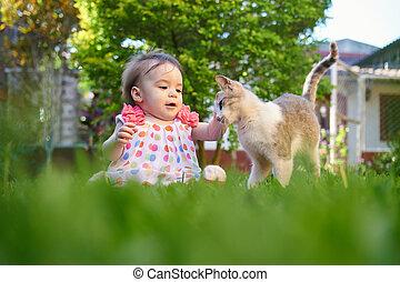Baby girl touching cat