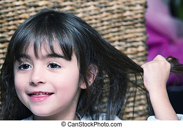 Baby girl touching hair while smiling