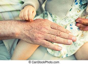 Baby girl touching hand of senior man