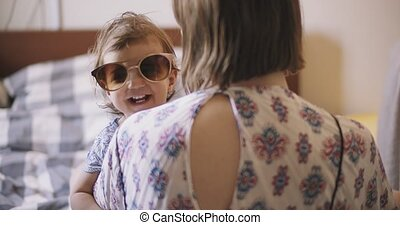 Baby girl trying on her mom's sunglasses.